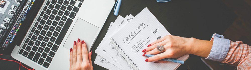 Mulher escrevendo na agenda em frente a um laptop