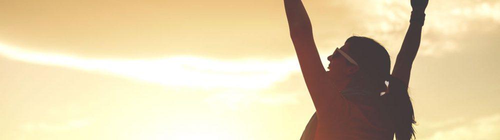 Mulher comemorando com os braços para cima em um pôr-do-sol