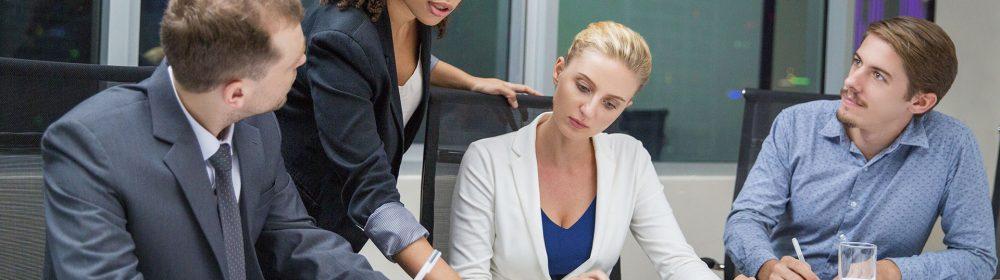 Líder e equipe de trabalho apontado para papeis sobre a mesa