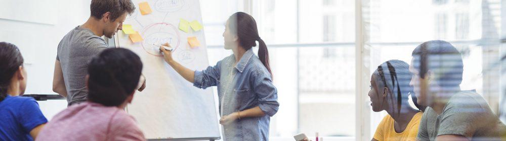 Pessoas em reunião escrevendo em um quadro