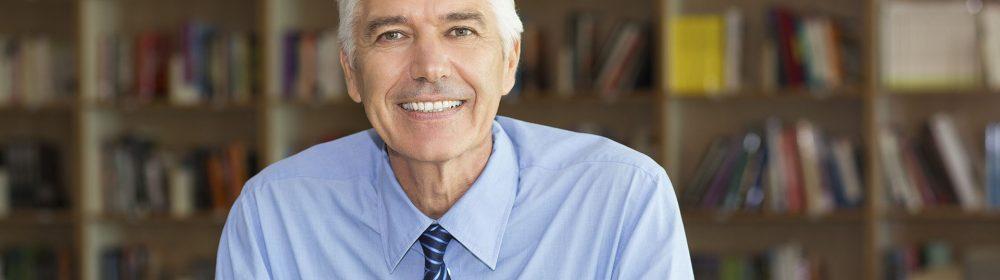 Homem de cabelo branco e gravata sorrindo